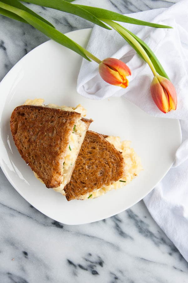 Grilled Cheese and Egg Sandwiches: fluffy scrambled eggs are smothered with melty mozzarella and sharp cheddar cheeses, nestled between two slices of buttery toasted bread.