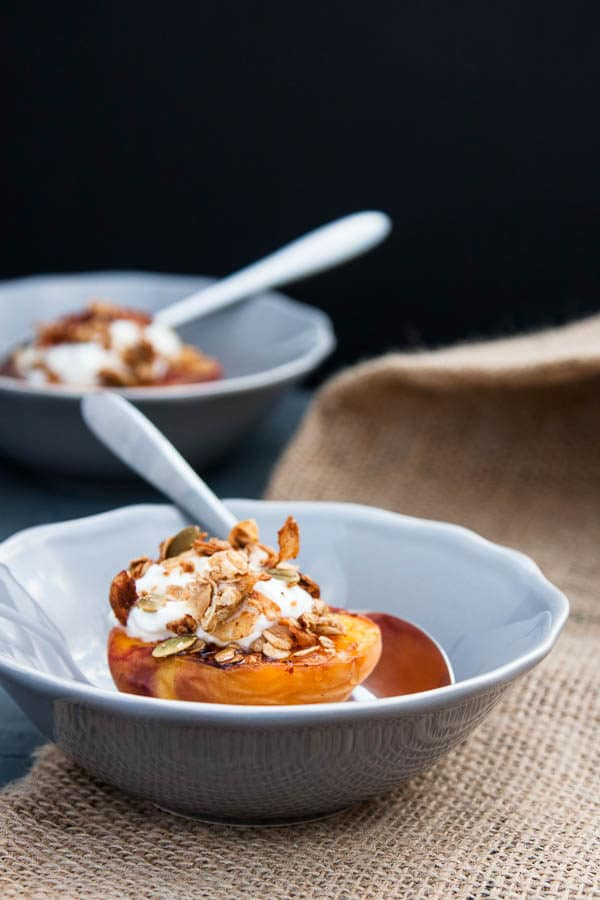 Grilled Peach Halves with Granola and Honey make a special variation on a fruit and granola breakfast - or swap the yogurt with vanilla ice cream for a light summer dessert!