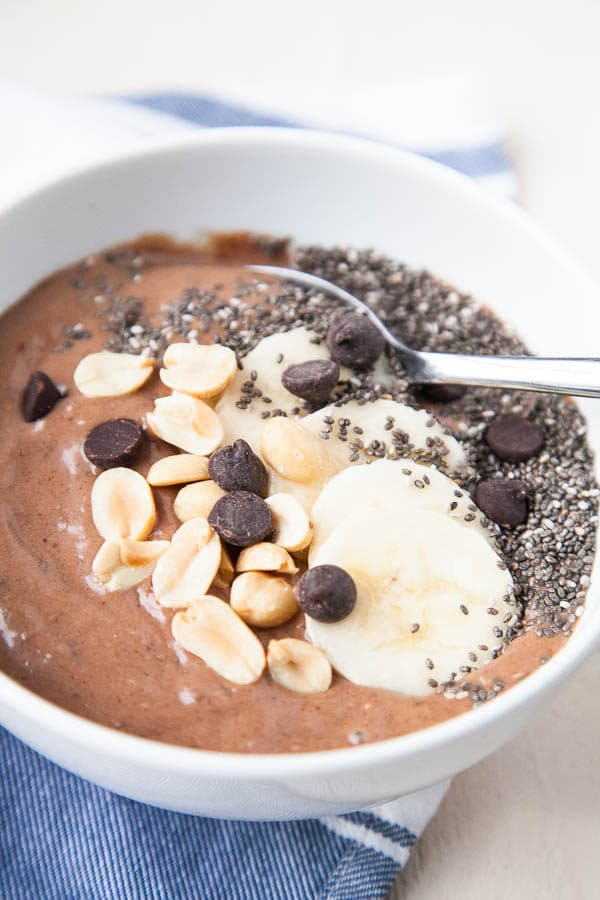 This Chocolate Peanut Butter Smoothie Bowl tastes like a treat, but is so healthy! Frozen bananas are mixed with a little almond milk, peanut butter, cocoa powder, dates for sweetness, and chia seeds for thickness.