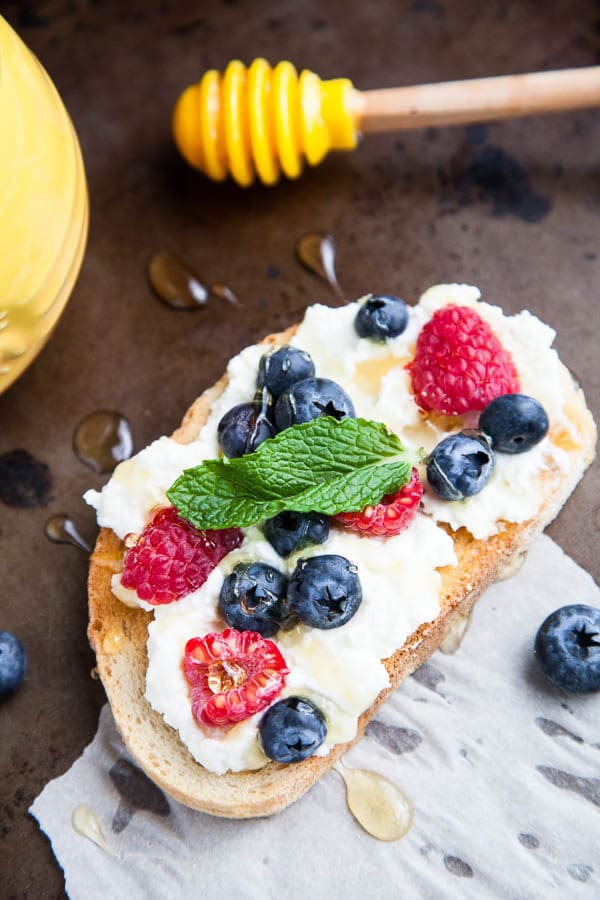 Generous smears of creamy ricotta cheese are paired with blueberries, raspberries, drizzled with lots of honey and tangy mint. A spring breakfast.