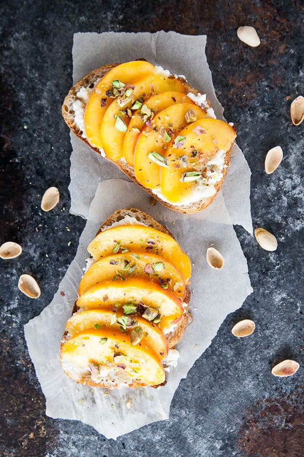 Enjoy peach ricotta toast for breakfast at the height of peach season - juicy sweet peaches are paired with creamy ricotta and crunchy salted pistachios.