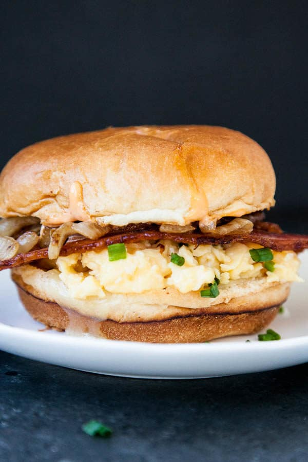 The Copycat Eggslut Sandwich is creamy scrambled eggs and chives inside a lightly toasted brioche bun, with cheddar cheese, caramelized onions, and sriracha mayo.
