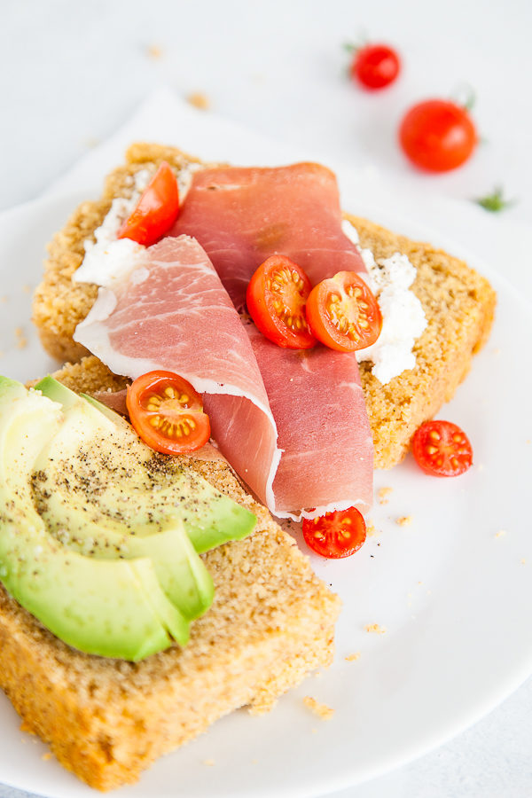 Slices of cornbread with prosciutto, tomatoes, and avocado on top.