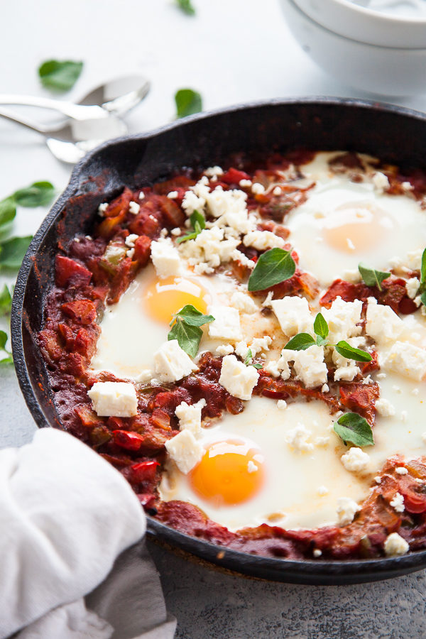Cast iron pan with Shakshuka and poached eggs